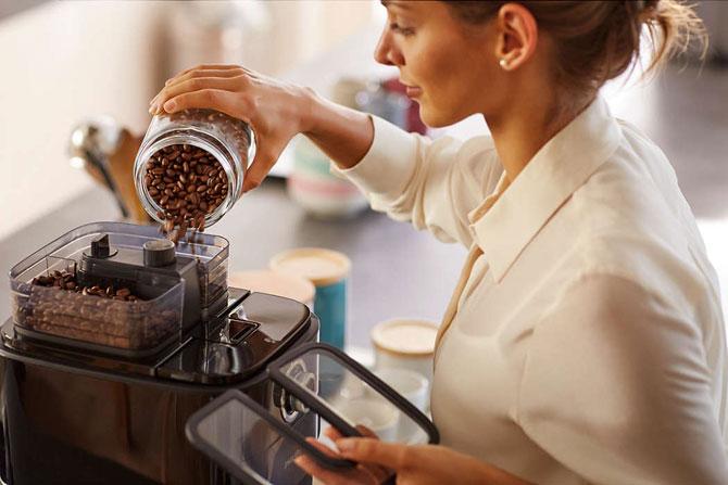 Насыпает кофейные зерна